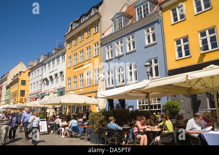 Copenhagen Denmark EU Visitors dining out in summer sunshine at open air cafes on Nyhavn with 17thc buildings - Stock Photo