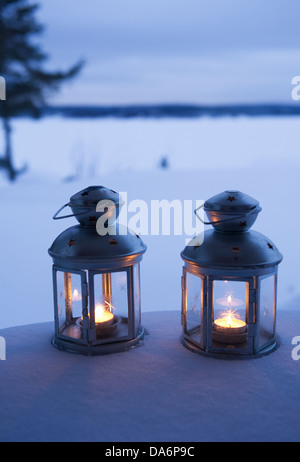 Close-up of glowing lantern in snow - Stock Photo