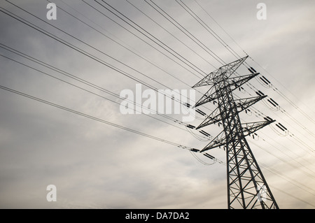 Power lines against an overcast grey and cloudy sky - Stock Photo