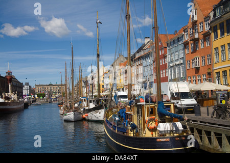 Copenhagen Denmark EU View along Nyhavn canal with moored sailing boats and colourful facades of 17thc buildings - Stock Photo