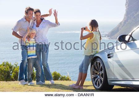 Girl photographing waving family outside car near ocean - Stock Photo