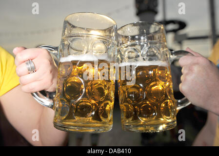 Two visitors clink their beer mugs at the Oktoberfest in Munich, Germany, 25September 2011. Until 03 October 2011, - Stock Photo