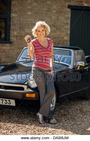 A mature woman holding the keys to classic sports car - Stock Photo