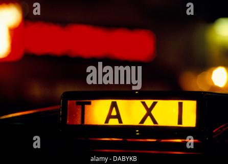 Taxi sign lit up at night London UK HOMER SYKES - Stock Photo