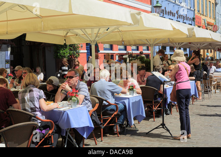 Busy outdoor cafés and restaurants with people dining out under sun umbrellas on street in summer. Nyhavn Copenhagen - Stock Photo