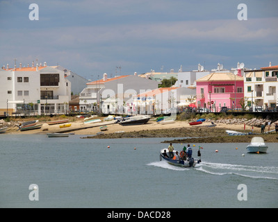 The town of Cabanas de Tavira with small boat taking tourists to and from the beach. Algarve region, Portugal - Stock Photo