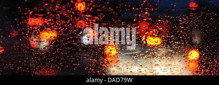 Cars a stuck in a traffic jam at a highway near Freiburg and the rear lights are reflected in the raindrops of a - Stock Photo