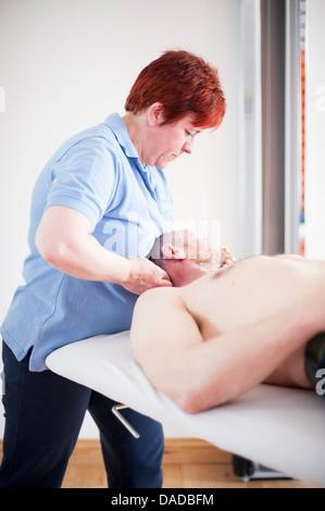 Man lying on back receiving head massage - Stock Photo