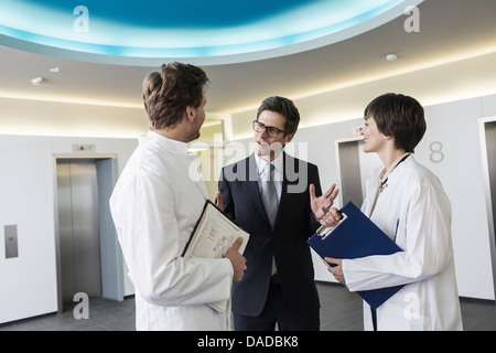Man and woman wearing lab coats having conversation in lobby with man wearing business attire - Stock Photo