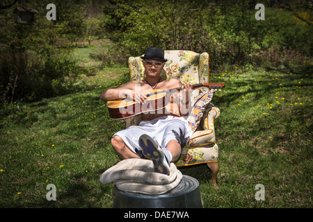 Man playing guitar sitting in armchair in garden - Stock Photo
