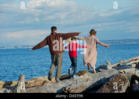 Back view of family walking along tree trunk at coast - Stock Photo