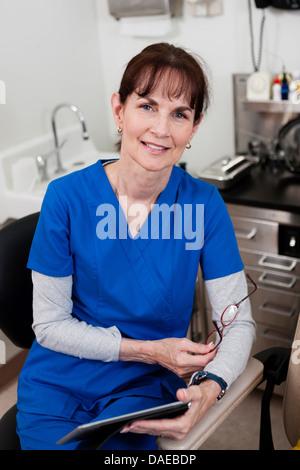 Senior doctor in blue scrubs holding medical chart, portrait - Stock Photo