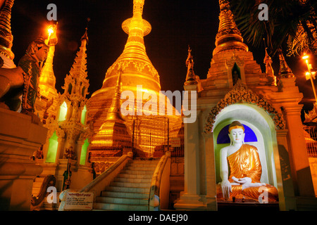 A BUDDHA STATUE and the main ZEDI of the SHWEDAGON PAGODA which dates from 1485 is gilded every year , MYANAMAR, - Stock Photo