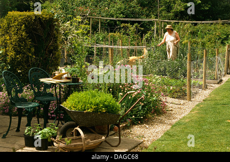 Woman standing in country vegetable garden with gravel path and green wrought iron chairs at table on patio - Stock Photo