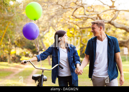 beautiful teenage couple walking in park holding hands - Stock Photo