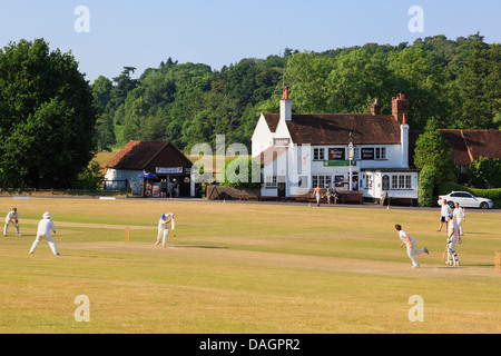 Local teams playing a cricket match on village green with scorched grass in front of Barley Mow pub on a summer - Stock Photo