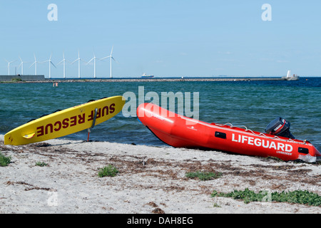 Lifeguard rescue board and inflatable boat on the beach at Kastrup, Copenhagen. Middelgrunden offshore wind park - Stock Photo