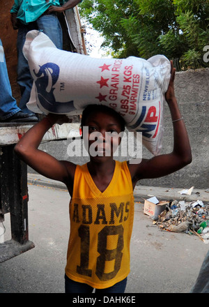 A young Haitian woman carries a 55-pound bag of rice distributed by the World Health Organization at a food distribution - Stock Photo