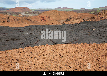 Hardened black pahoehoe lava flow over top of older oxidized and fragmented red aa lava flow with volcanic cones - Stock Photo