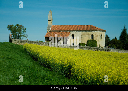 A small country church in southwest France is adorned in Spring by a field of bright yellow colza flowers--rapeseed - Stock Photo