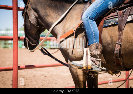 Detail shot of a young woman sitting on a horse wearing cowboy boots and spurs. - Stock Photo