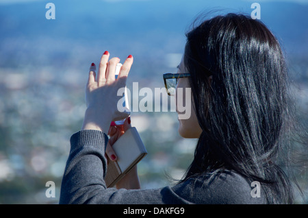 Japanese tourist taking a photograph on the top of Mount Eden, Auckland, New Zealand. - Stock Photo