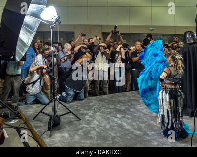 Under studio lighting, amateur photographers crowd photograph a model during a photo opportunity at a photographic - Stock Photo