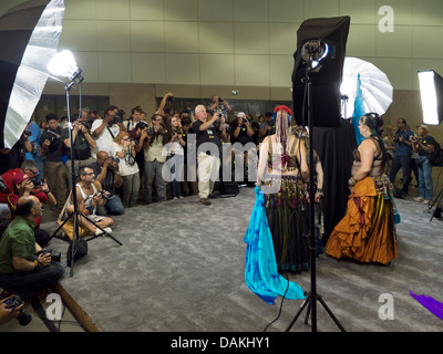 Under studio lighting, amateur photographers crowd photograph models during a photo opportunity at a photographic - Stock Photo