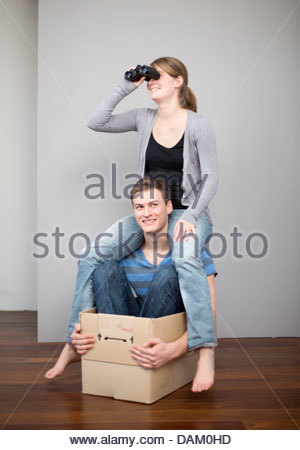 Young couple playing with a cardboard box and binoculars - Stock Photo