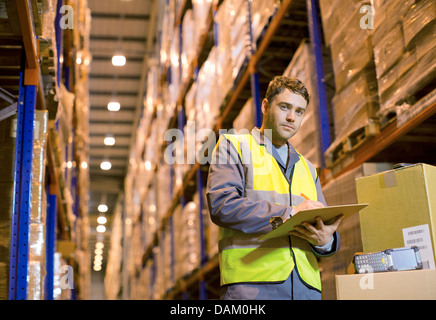 Worker writing on clipboard in warehouse - Stock Photo