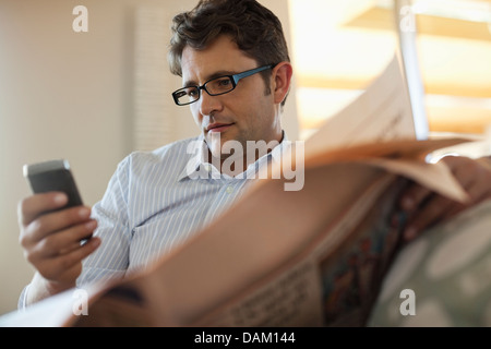 Man using cell phone and reading newspaper - Stock Photo