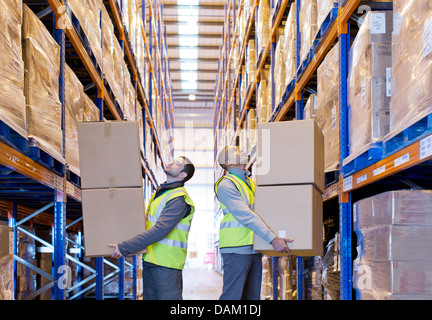Workers carrying boxes in warehouse - Stock Photo