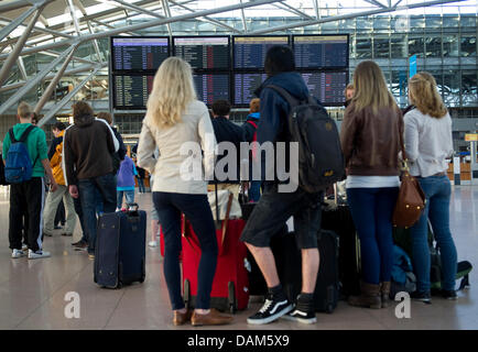 Passengers seek information in front of a destination board at the airport in Hamburg, Germany, 25 May 2011. An - Stock Photo