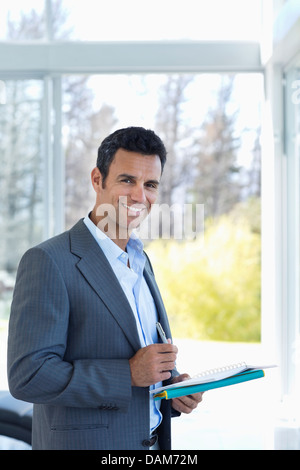 Businessman reading papers in office - Stock Photo