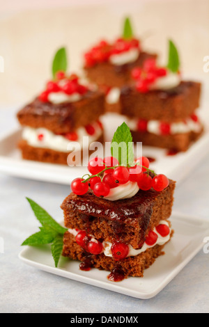Chocolate sponge cakes with red currants. Recipe available. - Stock Photo