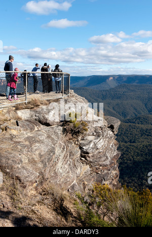 People on the viewing lookout rock, looking over the Jamison Valley, at Sublime Point, Blue Mountains, Australia - Stock Photo