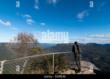 A man looks out over Jamison Valley in the Blue Mountains at Sublime Point, near Leura, Australia - Stock Photo