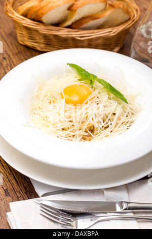spaghetti with egg on a table in a restaurant - Stock Photo