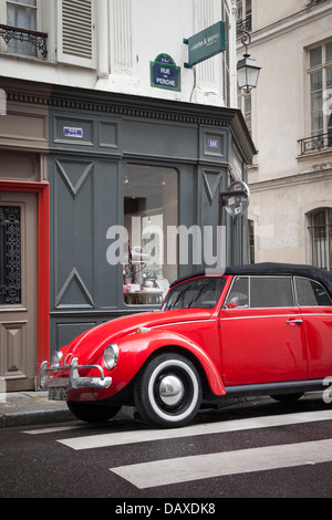 Red Volkswagen Beetle parked in front of consignment shop in the Marais, Paris France - Stock Photo
