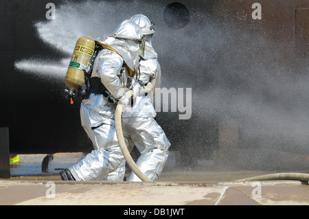 Senior Airman Larry Thompson and Airman 1st Class Nathan Smalkoski extinguish a plane fire during a training exercise - Stock Photo