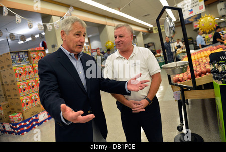 Secretary of Defense Chuck Hagel, left, tours the commissary at Naval Air Station Jacksonville, Fla., with store - Stock Photo
