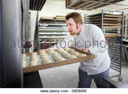 Chef baking buns in a bakery - Stock Photo