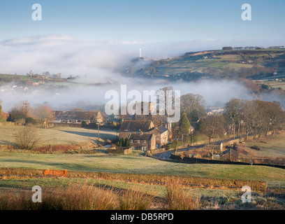 thinning mist cover revealing the church of st mary in oxenhope in the yorkshire dales - Stock Photo