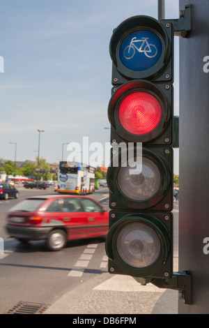 Traffic lights for cyclists, bicycle light turns red, a car cross the cycle way - Stock Photo