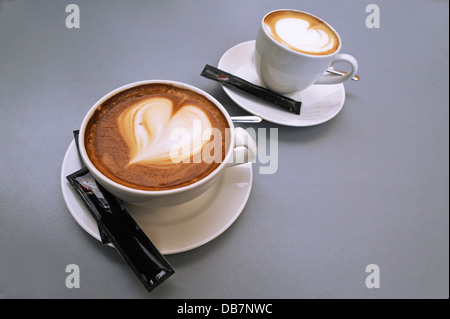A large cup and a small cup of cappuccino with a heart shape in the milk foam - Stock Photo