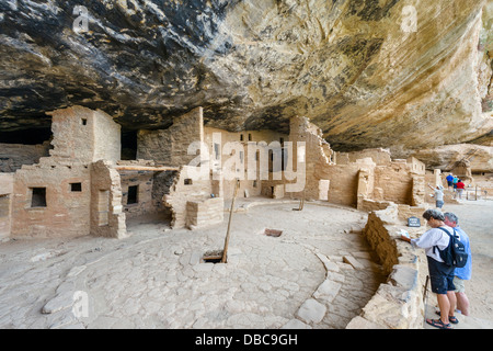 Tourists at Spruce Tree House ruins, ancient Anasazi pueblo dwellings, Mesa Verde National Park, Cortez, Colorado, - Stock Photo
