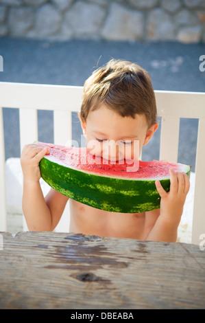 Little boy eating big slice of watermelon - Stock Photo