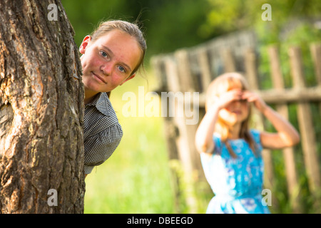 Sisters playing hide and seek in the park - Stock Photo