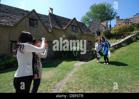 Asian tourists at Arlington Row, iconic row of 17th century Cotswolds cottages in Bibury, United Kingdom - Stock Photo