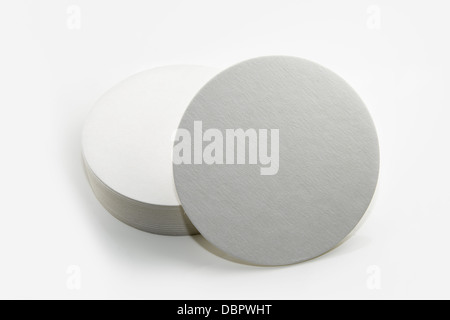 Stack of new beer coasters isolated on a white background.  Add your own design or logo. - Stock Photo